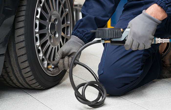 Mechanic Checking Tyre Pressure With Gauge